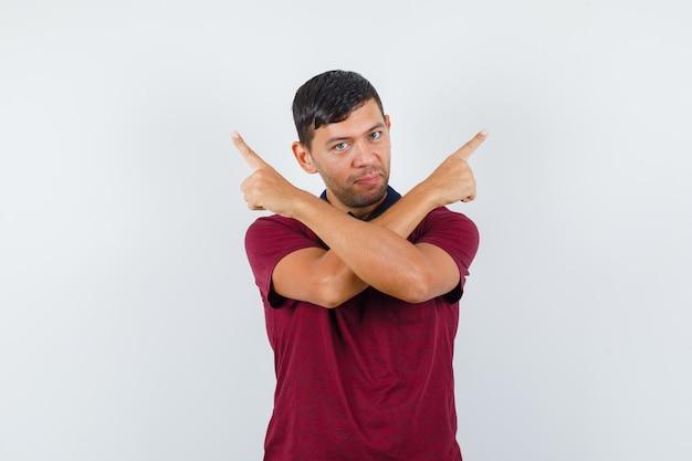 Jeune homme pointant vers le haut en t-shirt et ayant l'air confiant. vue de face.