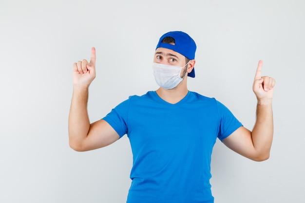 Jeune homme pointant vers le haut en t-shirt bleu et casquette, masque et à la confiance