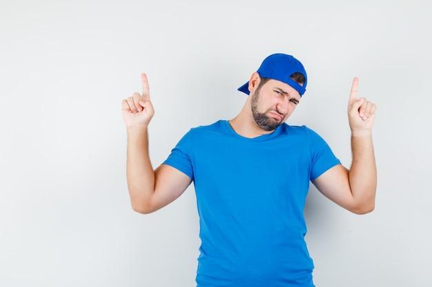 Jeune homme pointant vers le haut en t-shirt bleu et casquette et à la sans joie