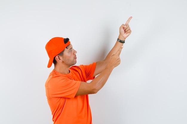 Jeune homme pointant vers le haut en t-shirt et casquette orange et à la recherche concentrée