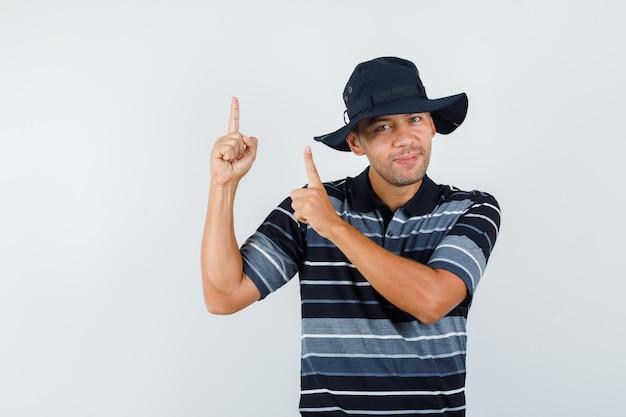 Jeune homme pointant vers le haut en t-shirt, chapeau et l'air heureux. vue de face.