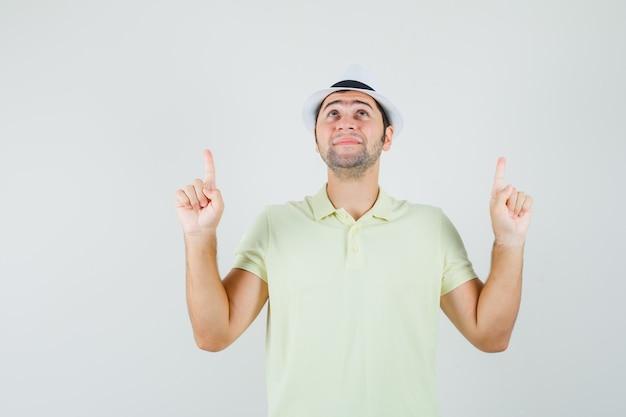 Jeune homme pointant vers le haut en t-shirt, chapeau et à la recherche d'espoir.