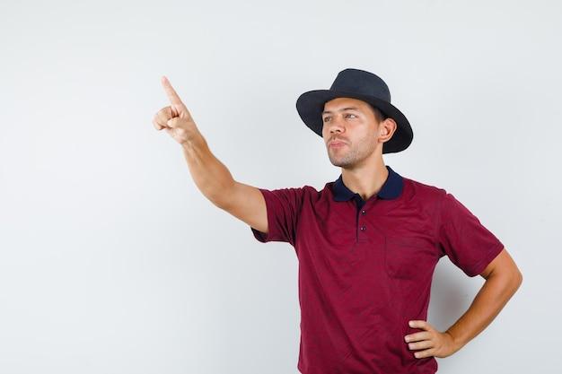 Jeune homme pointant vers le haut en t-shirt, chapeau et regardant concentré, vue de face.