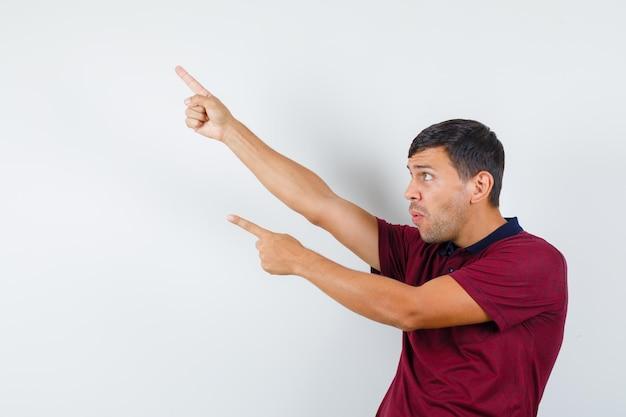 Jeune homme pointant vers le haut en t-shirt et regardant concentré, vue de face.