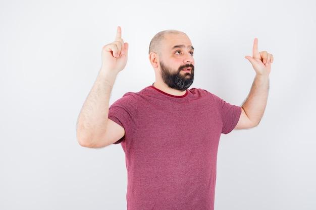 Jeune homme pointant vers le haut en t-shirt rose et l'air optimiste. vue de face.