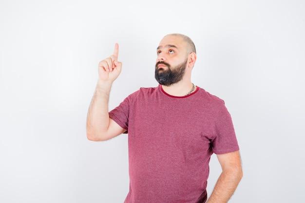 Jeune homme pointant vers le haut en t-shirt et se demandant. vue de face.