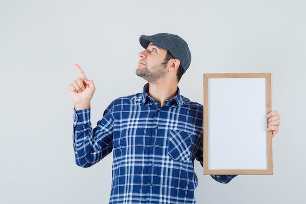 Jeune homme pointant vers le haut tout en tenant un cadre vide en chemise, casquette et à la vue de face, focalisée.