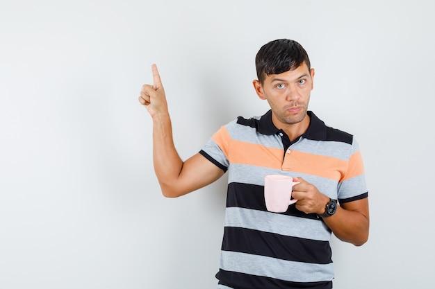 Jeune homme pointant vers le haut tout en tenant une tasse de boisson en t-shirt et à la recherche de sérieux
