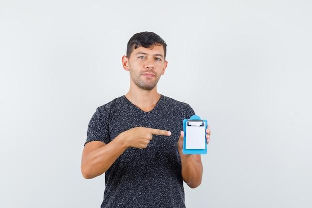 Jeune homme pointant vers un petit cahier en t-shirt noir et ayant l'air confiant, vue de face.