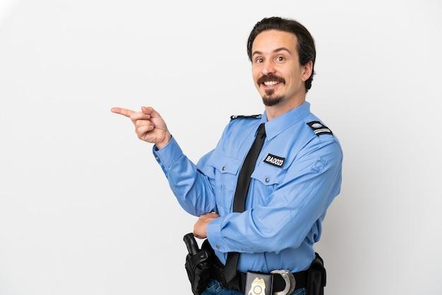 Jeune homme de police sur fond isolé blanc pointant le doigt sur le côté