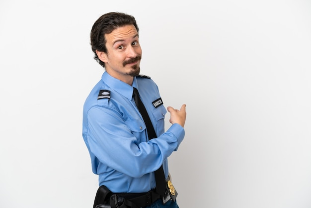 Jeune homme de police sur fond isolé blanc pointant vers l'arrière