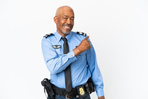 Jeune homme de police isolé sur fond blanc pointant vers l'arrière