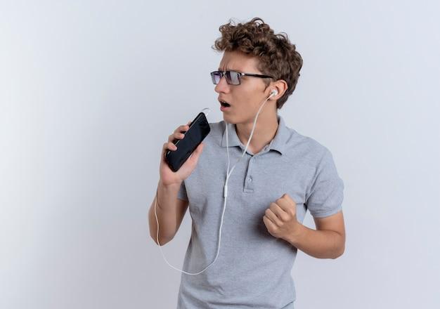 Jeune homme en polo gris avec des écouteurs tenant le smartphone à l'aide de chant microphone debout sur un mur blanc