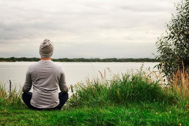 Un jeune homme en polo léger est assis sur le rivage. la vue de l'arrière. formation de yoga. apaisement.