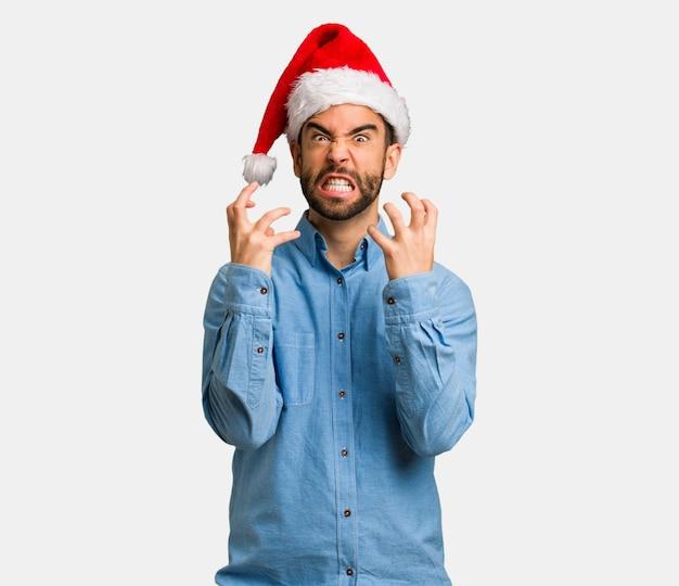 Jeune homme portant le bonnet de noel en colère et contrarié