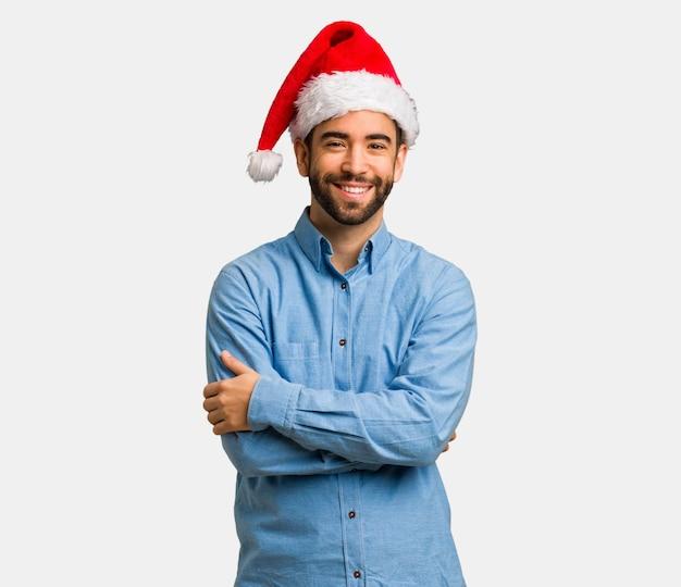 Jeune homme portant le bonnet de noel croisé les bras, souriant et détendu