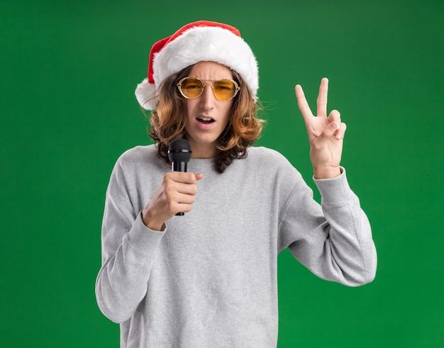 Jeune homme portant un bonnet de noel et des lunettes jaunes tenant un microphone souriant montrant un signe v debout sur un mur vert