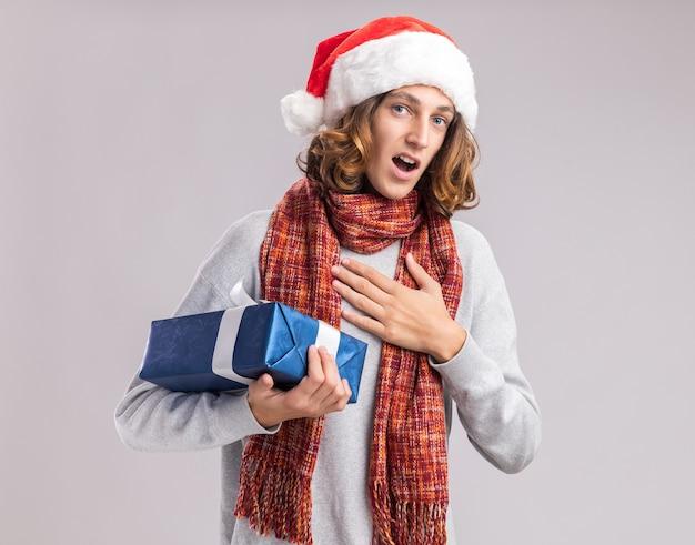 Jeune homme portant un bonnet de noel de noël avec une écharpe chaude autour du cou tenant un cadeau de noël à la surprise de se sentir reconnaissant debout sur un mur blanc
