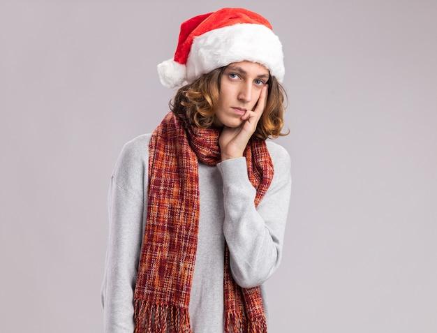 Jeune homme portant un bonnet de noel de noël avec une écharpe chaude autour de son cou à la pensée avec expression pensive