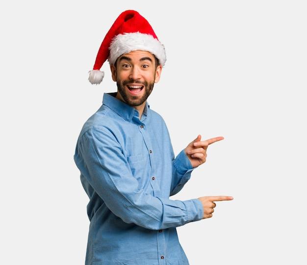 Jeune homme portant le bonnet de noel pointant sur le côté avec le doigt