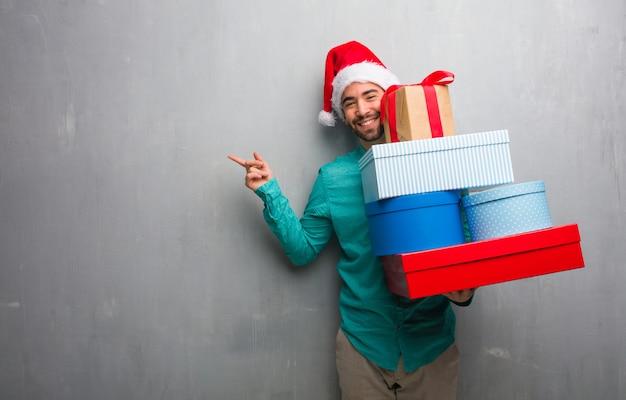 Jeune homme portant un bonnet de noel tenant des cadeaux pointant vers le côté avec le doigt