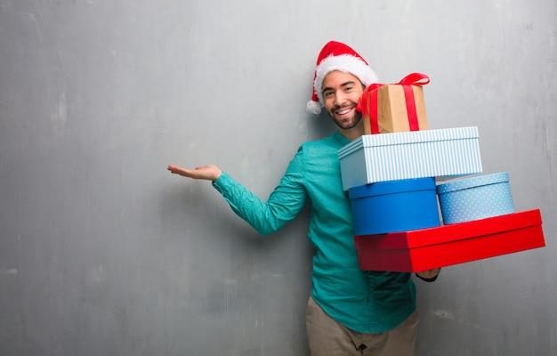 Jeune homme portant un bonnet de noel tenant des cadeaux tenant quelque chose avec la main