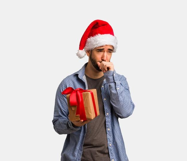 Jeune homme portant le bonnet de noel toussant, malade à cause d'un virus ou d'une infection