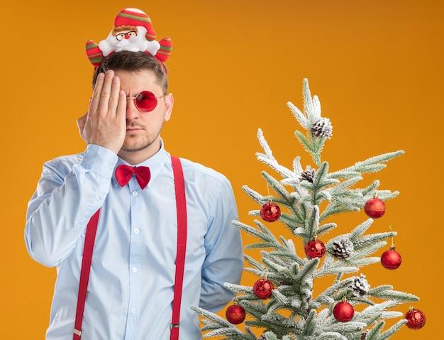 Jeune homme portant des bretelles noeud papillon en jante avec le père noël et des lunettes rouges debout à côté de l'arbre de noël couvrant un œil avec la main regardant la caméra sur fond orange