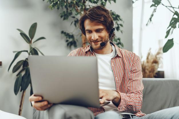 Jeune homme portant un casque faisant un appel vidéo par ordinateur portable à la maison