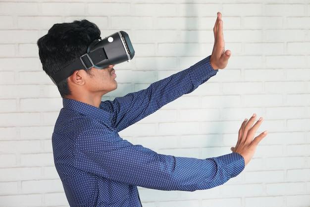 Jeune homme portant un casque de réalité virtuelle, boîte vr isolé sur blanc