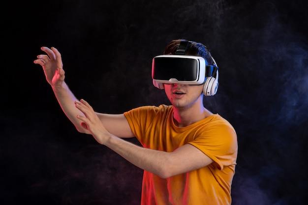 Jeune homme portant un casque de réalité virtuelle sur la surface sombre
