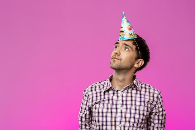 Jeune homme portant un chapeau d'anniversaire sur mur violet. fête d'anniversaire.