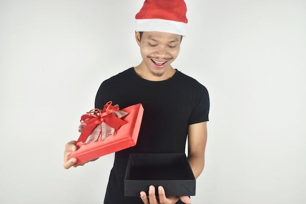 Jeune homme portant un chapeau de noël boîte cadeau d'ouverture heureuse