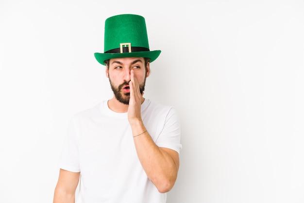 Jeune homme portant un chapeau de saint patrick dit une nouvelle secrète sur le freinage à chaud et regarde de côté