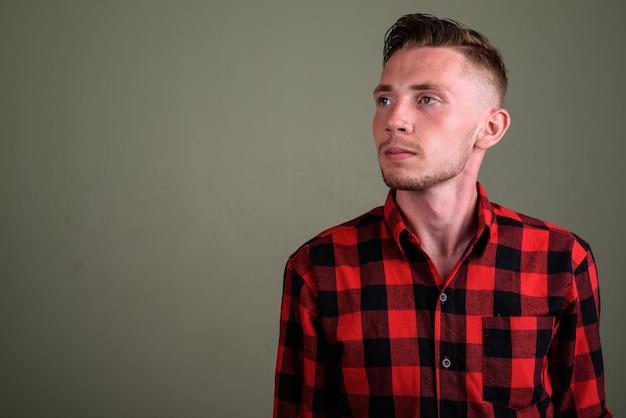 Jeune homme portant une chemise à carreaux rouge contre un mur de couleur