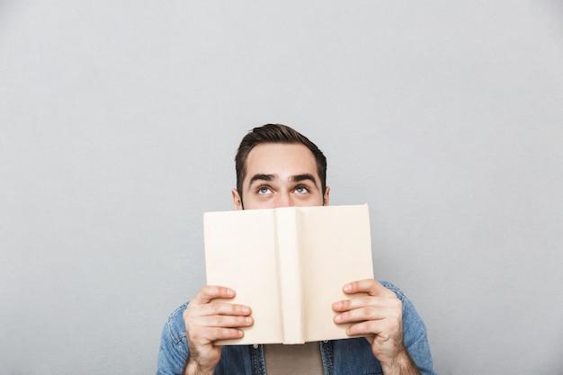 Jeune homme portant une chemise isolée sur un mur gris, couvre le visage avec un livre ouvert