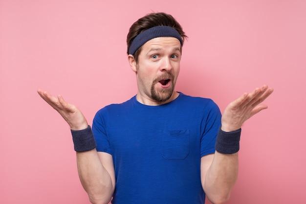 Jeune homme portant une chemise de sport choqué par une expression de surprise et un visage excité.