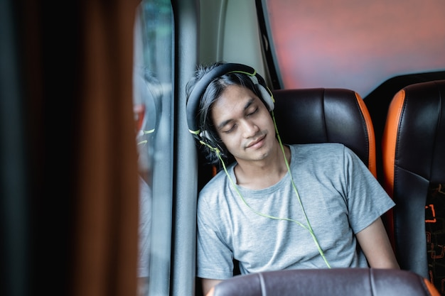 Un jeune homme portant des écouteurs de sommeil est appuyé contre la fenêtre alors qu'il était assis près de la fenêtre lors d'un voyage en bus