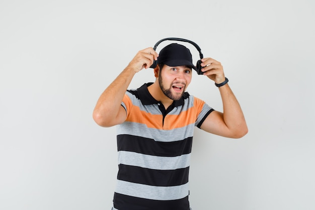 Jeune homme portant des écouteurs en t-shirt, casquette et à la joyeuse.
