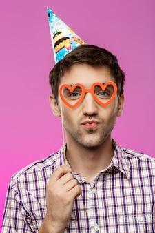 Jeune homme portant de fausses lunettes sur mur violet. fête d'anniversaire.