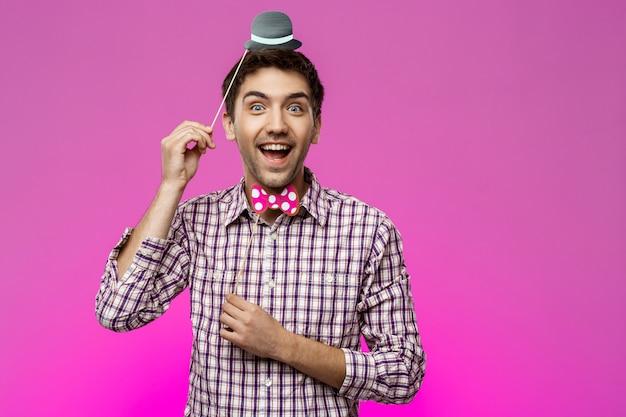 Jeune homme portant un faux chapeau et papillon sur mur violet.