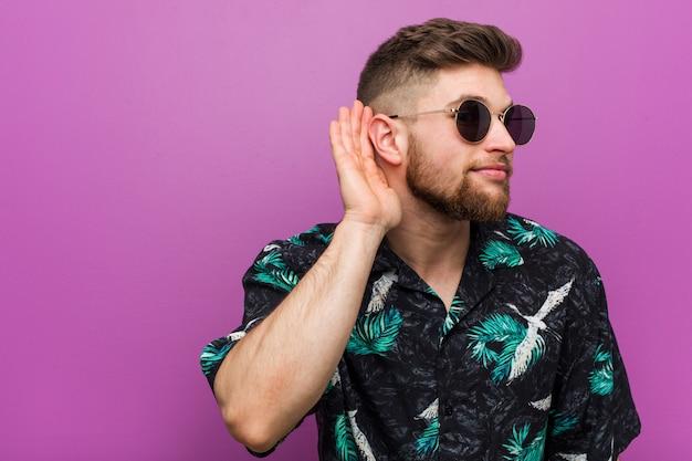 Jeune homme portant un look de vacances essayant d'écouter un commérage.