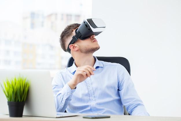 Jeune homme portant des lunettes de réalité virtuelle dans un bureau moderne.