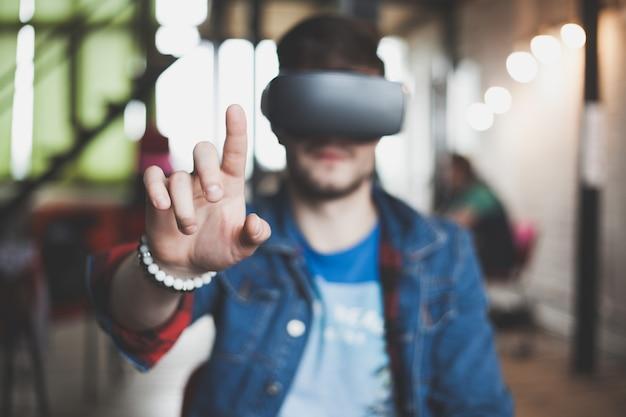 Jeune homme portant des lunettes de réalité virtuelle dans un studio de coworking de design d'intérieur moderne. smartphone utilisant avec un casque de lunettes vr.
