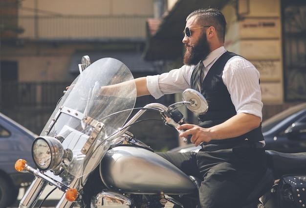 Jeune homme portant des lunettes de soleil et assis sur une moto