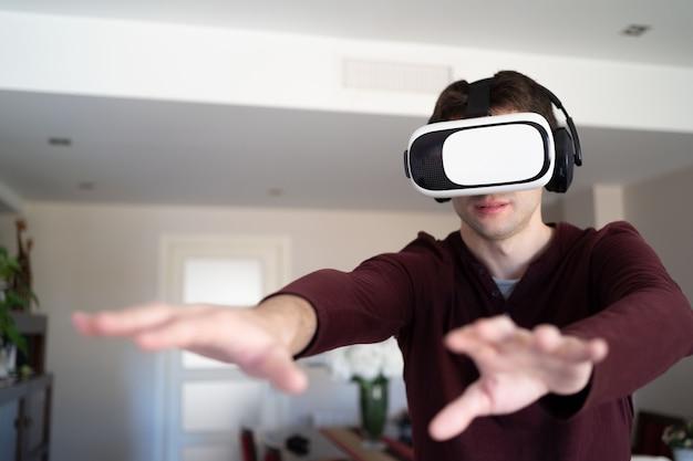 Jeune homme portant des lunettes vr à la maison et des bras en mouvement