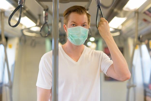 Jeune homme portant un masque de protection contre l'épidémie de virus corona à l'intérieur du train