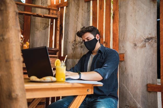 Jeune homme portant un masque de protection dans un bar