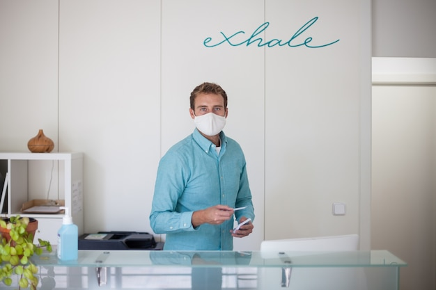 Jeune homme portant un masque à la réception du club de remise en forme moderne