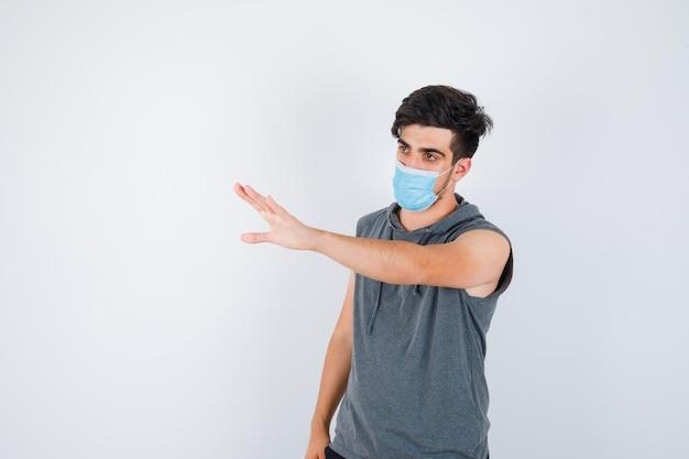 Jeune homme portant un masque tout en étirant les mains vers la gauche en t-shirt gris et l'air sérieux